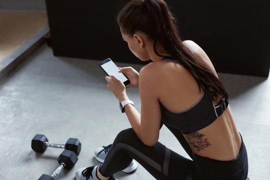 Sports Woman In Fashion Sportswear Using Phone On Training