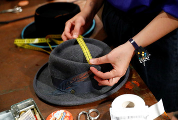 Lydia Bosche, hatter at headwear manufacturer Hut Styler measures the size of a hat at their workshop in Berlin