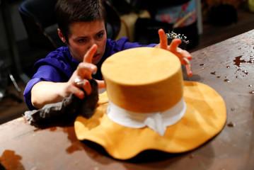 Lydia Bosche, hatter at headwear manufacturer Hut Styler works on a hat at their workshop in Berlin