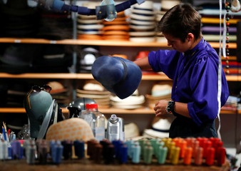 Lydia Bosche, hatter at headwear manufacturer Hut Styler forms a hat at their workshop in Berlin
