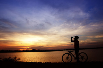 silhouette of the man drinking water with beautiful at sunset