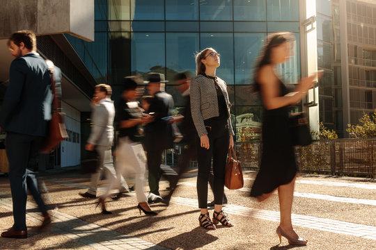 Businesswoman standing still on a busy street