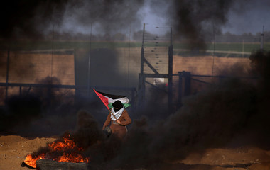 Woman holds a Palestinian flag during a protest at the Israel-Gaza border fence, in the southern Gaza Strip