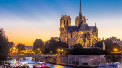 Rear view of Notre Dame De Paris cathedral day to night timelapse after sunset.