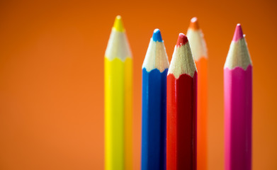 Wall Mural - Set of multicoloured  pencil or crayon on orange background.Selective focus