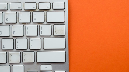 Wall Mural - Top view white keyboard on orange background