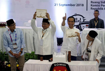 Indonesian President Joko Widodo and his opponent in next year's presidential elections Prabowo Subianto hold their ballot numbers during a ceremony at the election commission headquarters in Jakarta