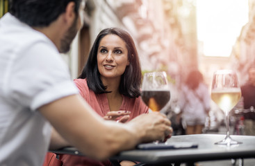 Togetherness concept: couple of friends talking, smiling and drinking in a bar table outdoor. Filtered image, focus on woman eyes.