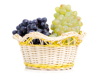 Black and white grapes in a basket on a white background isolation