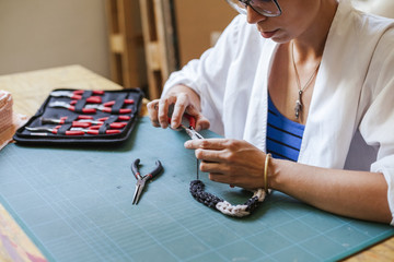 Young woman making jewelry in his laboratory