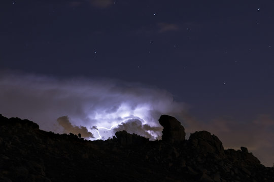 Rays and clouds in night storm over the mountain under a starry sky