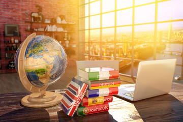 Languages learning and translate, communication and travel concept, books with covers in colors of flags of Europe countries, laptop and globe on a table in a modern interior Wall mural