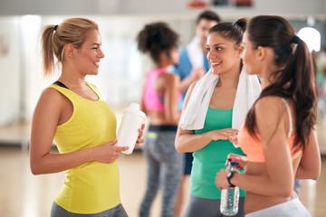 Women talking and refreshing on break in fitness class