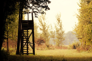 Autumn nature with a hunting tower on a field