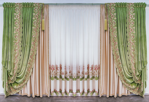 Decoration of the interior of the living room in the classical, palace style. Curtains made of green silk velvet fabric with ornament, and tulle with embroidery