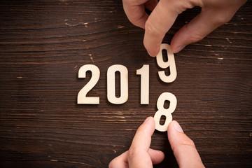 Hand verändert Ziffern und symbolisiert den Jahreswechsel zwischen 2018 und 2019 auf rustikalem Holzuntergrund