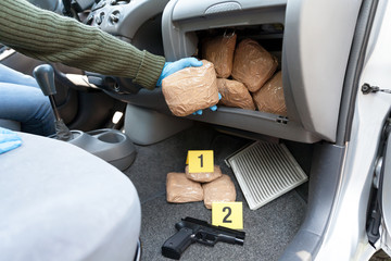 Police officer holding drug package found in secret compartment in a car
