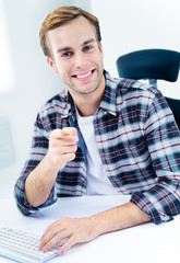 Smiling man in casual clothing, pointing at you
