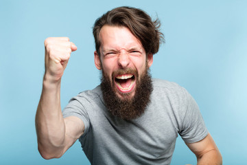 victory success and achievement. excited thrilled agitated guy making a win gesture. hipster man portrait on blue background. emotional reaction and facial expression concept. Wall mural
