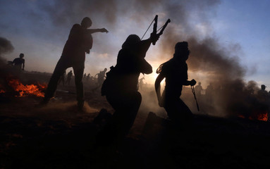 Palestinians hurl stones at Israeli troops during a protest at the Israel-Gaza border fence, in the southern Gaza Strip