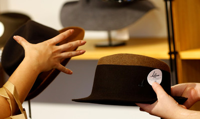 An employee of headwear manufacturer Muehlbauer and a customer hold hats in the company's store in Vienna