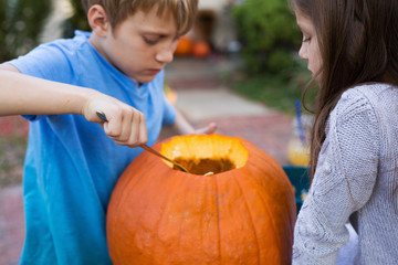 Siblings making jack-o-lanterns out of pumpkins.