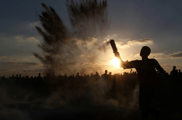 Palestinian returns a tear gas canister fired by Israeli troops during a protest at the Israel-Gaza border fence, in the southern Gaza Strip