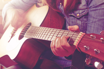 Young woman playing guitar and holding fingers chord. Close-up photo with pink light. With a hand blurred motion.