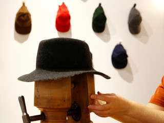 An employee of headwear manufacturer Muehlbauer adjusts a hat in the company's store in Vienna