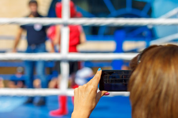 The woman make video with smartphone in front of boxing ring with child