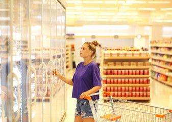 Woman choosing frozen food from a supermarket freezer