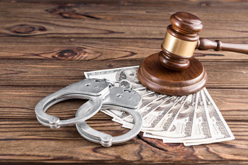 Handcuffs, American dollar bills on a wooden background, hammer of a judge. a bribe, arrest, bail, detention of a criminal.