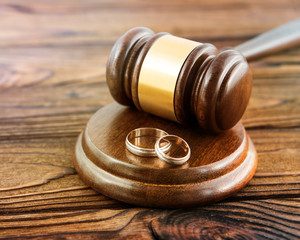 hammer of a judge, a pair of gold wedding rings on a wooden background. family law, divorce and conflict.
