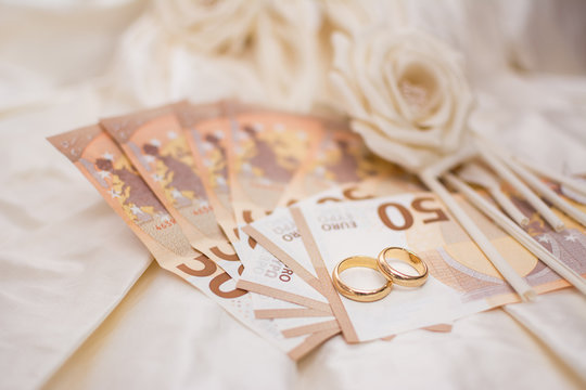 Wedding rings and banknotes with a wedding dress on the background