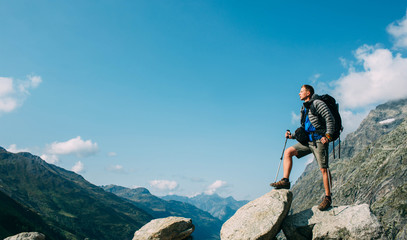 Hiker man with a backpack, on the mountain peak near pass Grand Ferret . Hiking around Mont Blanc, Switzerland part Wall mural