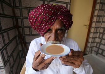 An elderly man wearing a traditional turban sips tea from a saucer as he poses for a picture outside his house on the outskirts of Ahmedabad