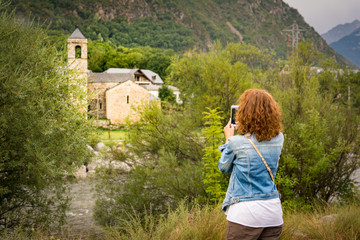 Girl taking a picture with a smartphone of the romanesque church of Sant Feliu de Barruera, in catalan Pyrenees.