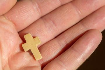 Hand offen mit kleinem Kreuz aus Holz