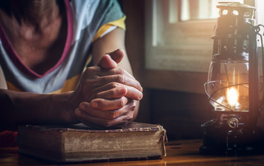 focus on hands of old woman while praying on Bible with oil lamp, christian concept