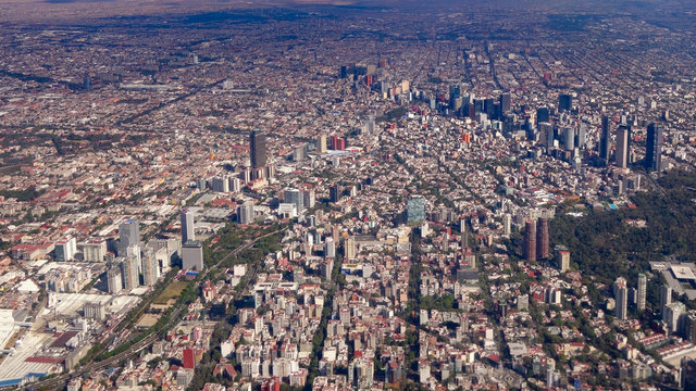 Mexico City, Mexico - Jan 2016: A Volaris passenger plane flies over the skyscrapers and parks of the central business district of Mexico City