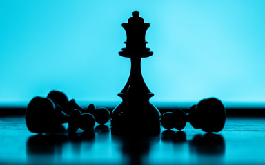 Pawns lying around a Queen chess piece on a blueish background