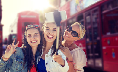summer vacation, holidays, travel, technology and people concept- group of smiling young women taking picture with smartphone on selfie stick over london city street background