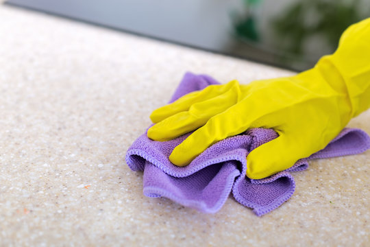 Woman's hands cleaning kitchen top