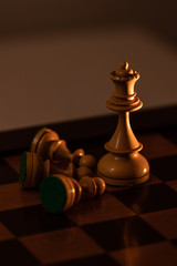 King Chess Piece lying on the side of Queen piece in the chessboard