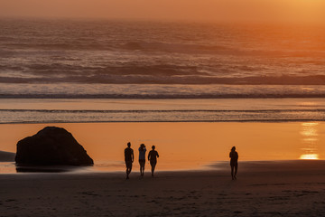 Sunset on Cannon Beach. Silhouettes of group of friends on the beach. Oregon, USA.