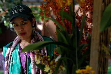 A woman looks at orchids during the National Orchid Exhibition at the Jose Celestino Mutis Botanical Garden in Bogota