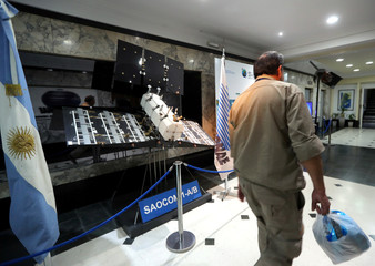 A man walks past a scaled-down replica of the SAOCOM 1-A/B satellite on display at Argentina's space agency CONAE in Buenos Aires