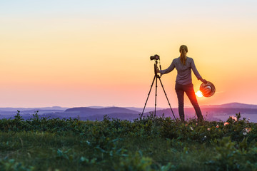Woman is photographing sunset. Enjoying spending time with camera in nature