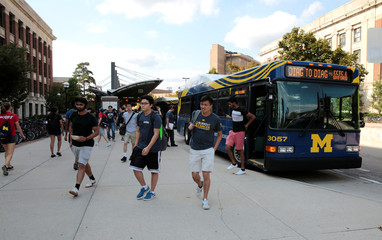 Students take the bus at the Central Campus Transit System at the University of Michigan in Ann Arbor