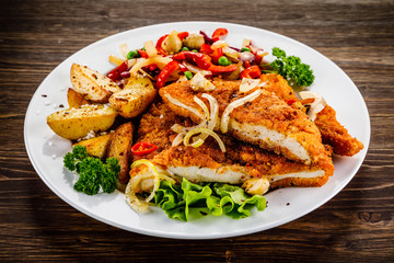 Fried pork chop with potatoes and vegetable salad on wooden background